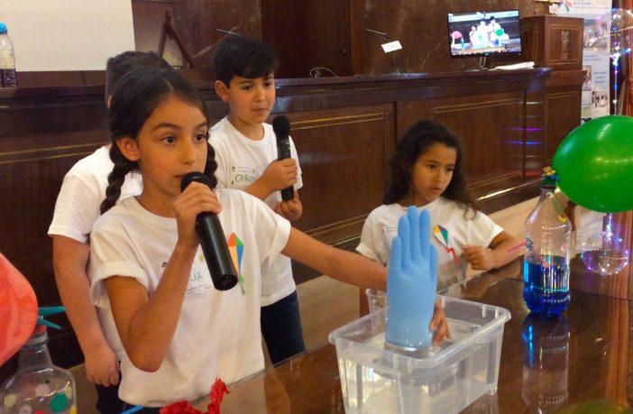 Una alumna del colegio Colegio Clara Campoamor, de Bormujos (Sevilla), explica por qué el guante se llena de aire en una cubeta de agua durante el VIII Encuentro Científico de El CSIC en la Escuela.