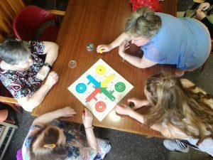 Dos alumnas del Politécnico de Estella (Navarra) juegan al parchís con dos mujeres mayores en una residencia.