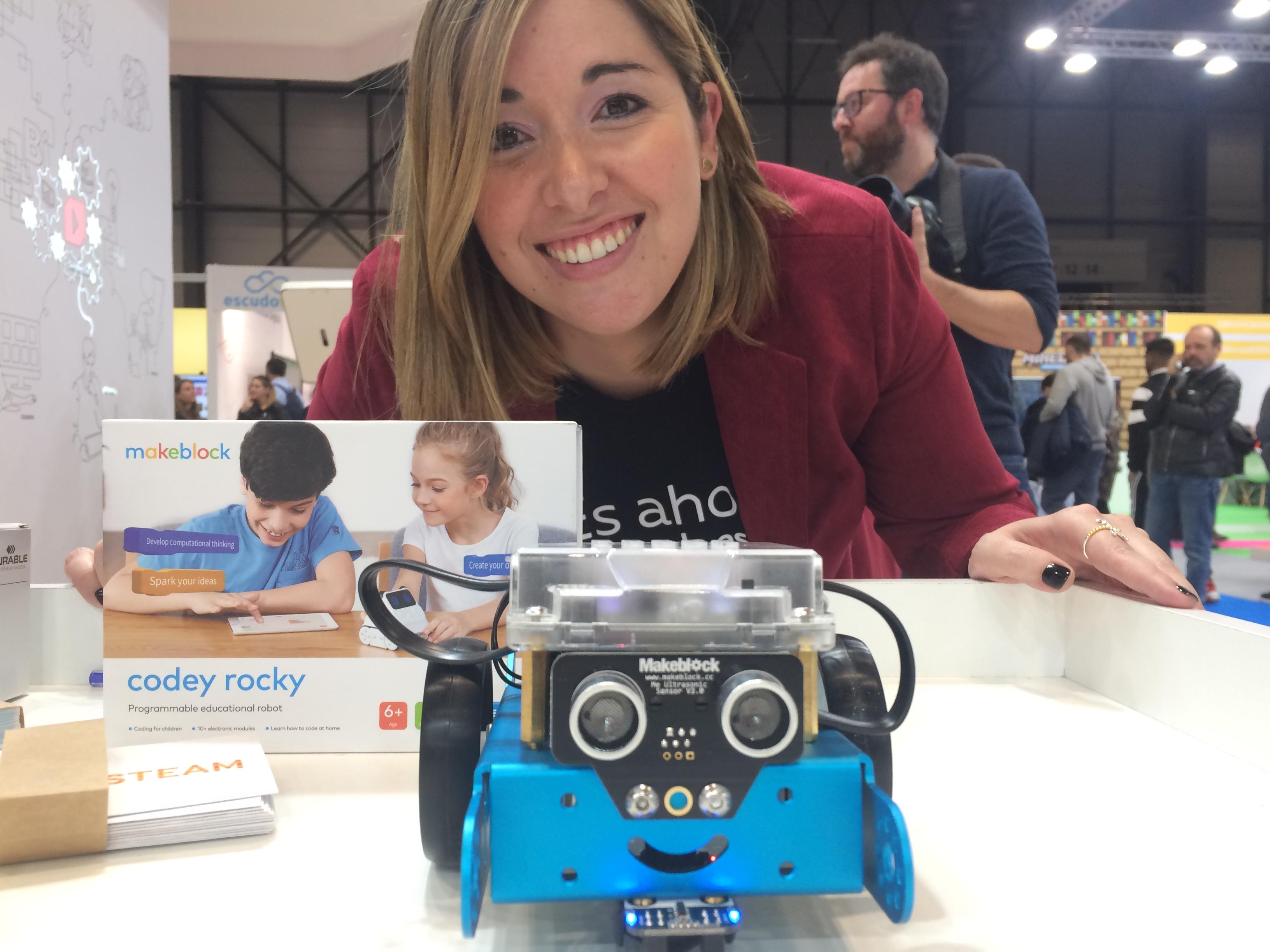 Esther Rodríguez, responsable pedagógica de Robótica de SM, posa con los robots Codey Rocky y M-Bot, en la feria SIMOEDU de 2019.